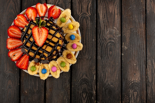 Vista dall'alto deliziose frittelle deliziose insieme a fette di fragole rosse e banane all'interno del piatto bianco su fondo di legno marrone