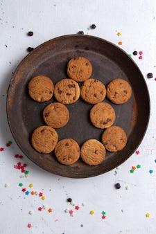 Vista dall'alto deliziosi biscotti al cioccolato all'interno del piatto rotondo scuro sullo sfondo bianco biscotto zucchero dolce tè