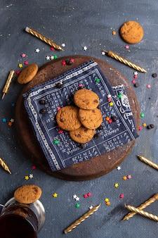 Vista dall'alto deliziosi biscotti al cioccolato con candele sullo sfondo grigio scuro biscotto zucchero dolce