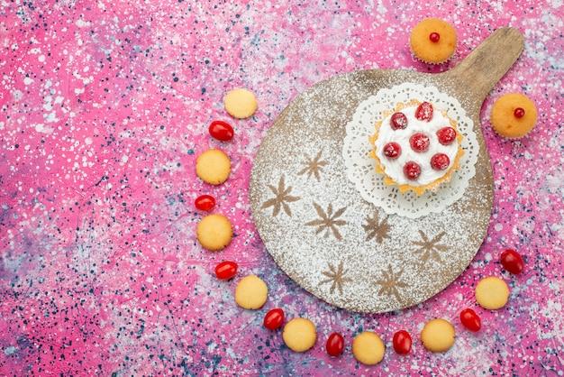 Vista dall'alto deliziosi biscotti con frutti rossi e torta sul dolce luminoso dello zucchero del biscotto della scrivania