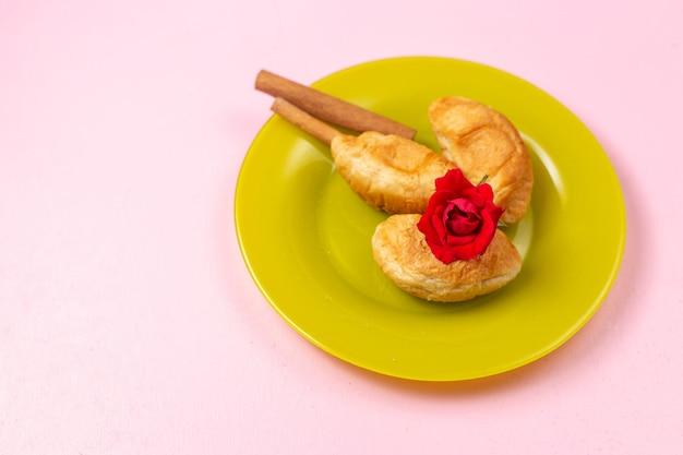 Vista dall'alto deliziosi croissant al forno con ripieno di frutta all'interno con cannella all'interno del piatto verde su sfondo rosa