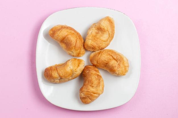 Vista dall'alto deliziosi croissant al forno con ripieno di frutta all'interno sulla scrivania rosa