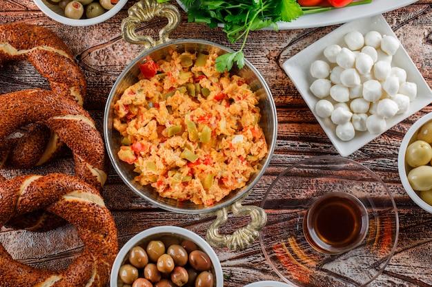 Vista dall'alto delizioso pasto nel piatto con bagel turco, una tazza di tè, insalata, sottaceti su superficie di legno