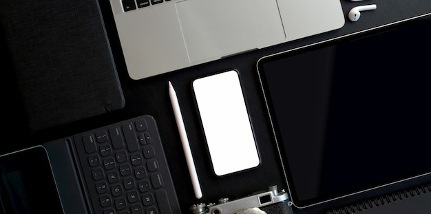 Vista dall'alto dell'area di lavoro alla moda scura con smartphone schermo vuoto e altri dispositivi elettronici con forniture per ufficio