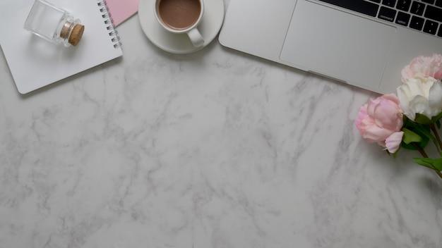 Vista dall'alto dell'area di lavoro con copia spazio, laptop, articoli per ufficio e tazza di tè sul tavolo di marmo