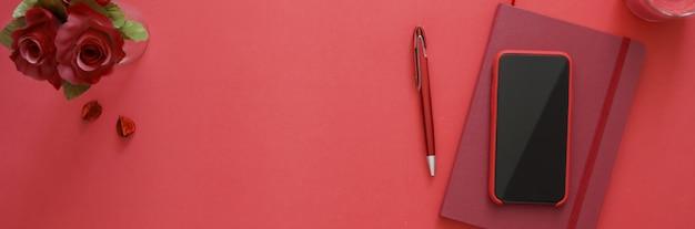 Vista dall'alto dell'area di lavoro con copia spazio, smartphone, taccuino del diario, cancelleria e vaso di rose sul tavolo rosa