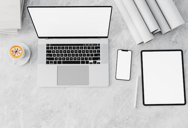 Vista dall'alto dell'area di lavoro con lo schermo del computer portatile in bianco sul tavolo