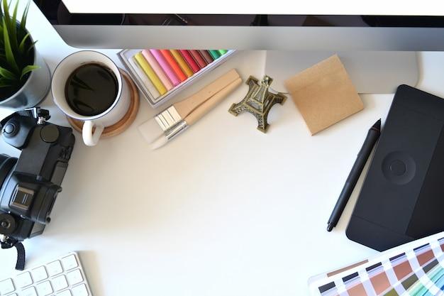 Vista dall'alto dell'area di lavoro del designer, computer, forniture creative e spazio per la copia