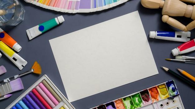 Vista dall'alto dell'area di lavoro del designer con carta da schizzo e strumenti di pittura