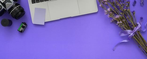 Vista dall'alto dell'area di lavoro del fotografo con laptop, fotocamera, fiori e copia spazio sulla scrivania viola
