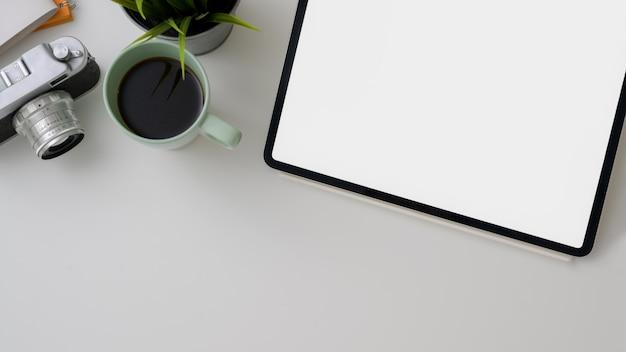 Vista dall'alto dell'area di lavoro del fotografo con tablet schermo vuoto, fotocamera, tazza di caffè e copia spazio