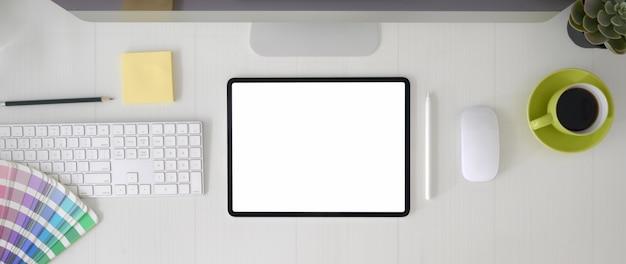 Vista dall'alto dell'area di lavoro del progettista grafico con tablet schermo vuoto, dispositivo informatico e materiali di consumo