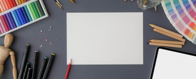 Vista dall'alto dell'area di lavoro dell'artista con strumenti di schizzo di carta, campione di colore, tablet e pittura