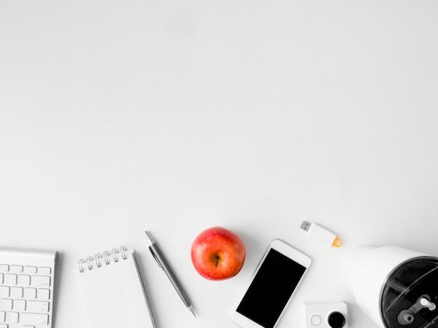 Vista dall'alto dell'area di lavoro della scrivania con notebook, telefono e gadget su sfondo bianco, graphic designer, concetto di designer creativo.