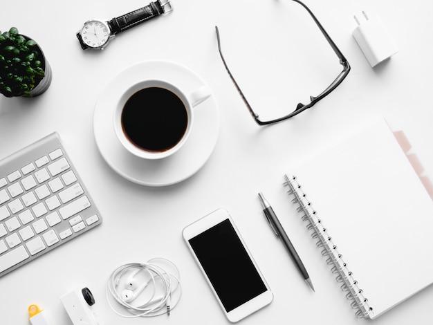 Vista dall'alto dell'area di lavoro della scrivania con tazza di caffè, taccuino, pianta di plastica, tavoletta grafica su sfondo bianco con spazio di copia, graphic designer, concetto di designer creativo.