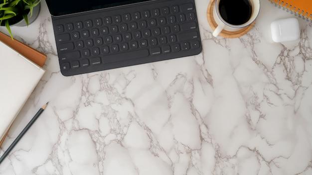 Vista dall'alto dell'area di lavoro di design moderno con tavoletta digitale, tazza di caffè, articoli di cancelleria e copia spazio