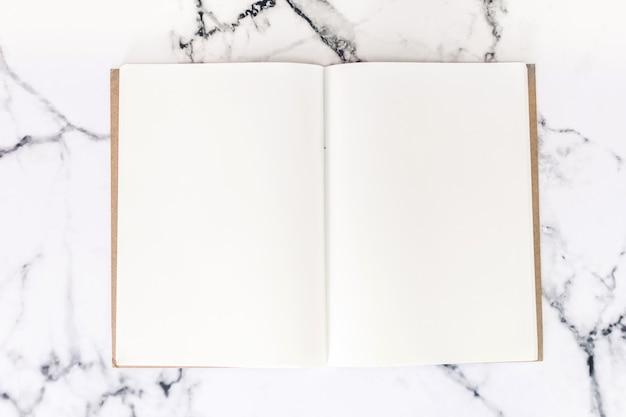 Vista dall'alto dell'area di lavoro e notebook aperto con mock up di pagine vuote