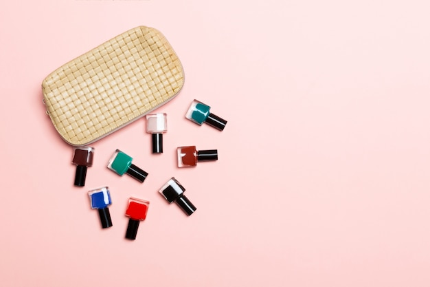 Vista dall'alto dell'insieme di smalti e smalti gel luminosi caduti dalla borsa dei cosmetici con spazio di copia su sfondo rosa. unghia alla moda