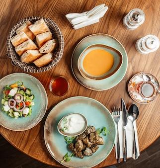 Vista dall'alto dell'installazione del pranzo con zuppa di lenticchie di dolma e insalata di verdure con formaggio
