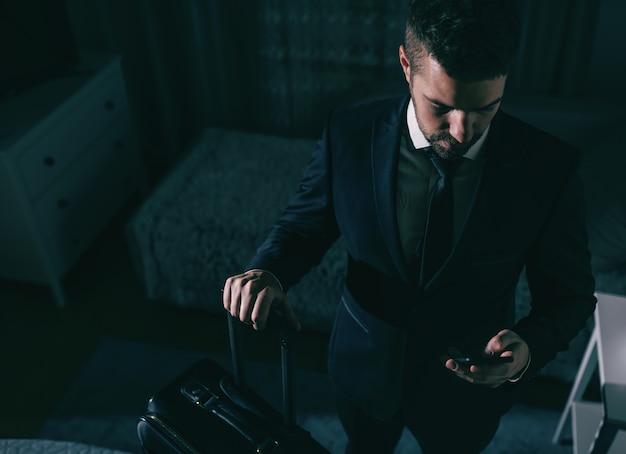 Vista dall'alto dell'uomo d'affari in tuta in piedi in camera da letto, tenendo la valigia e utilizzando smart phone. concetto di viaggio d'affari.