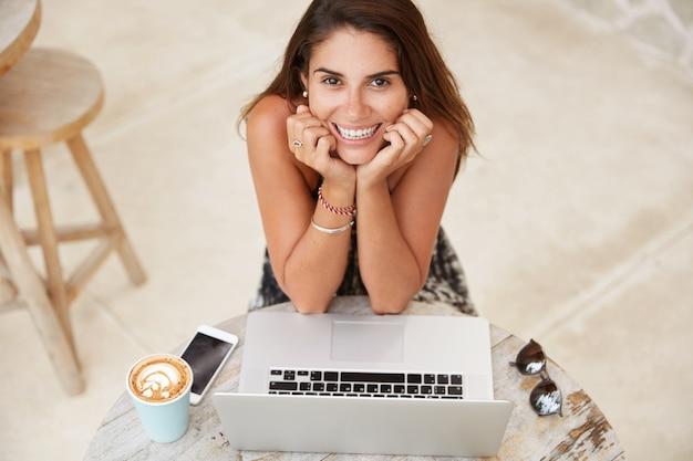 Vista dall'alto della bella giovane donna stupita guarda con espressione stupita alla telecamera, naviga le informazioni sul computer portatile