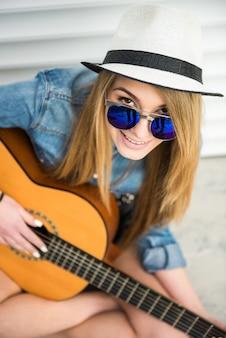 Vista dall'alto della bella ragazza alla moda con la chitarra acustica.