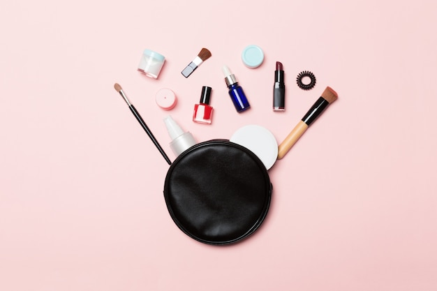 Vista dall'alto della borsa per cosmetici con prodotti per il trucco versati sul rosa