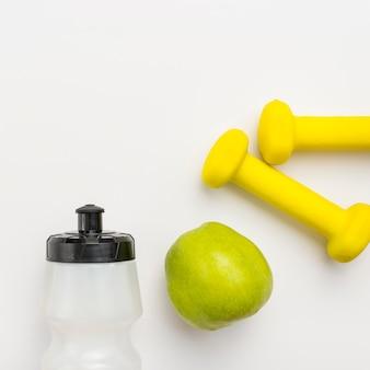 Vista dall'alto della bottiglia d'acqua con mela e pesi