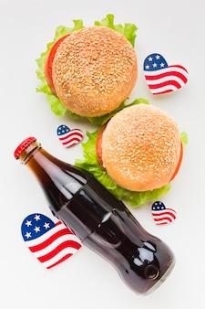 Vista dall'alto della bottiglia di soda con hamburger e bandiere americane