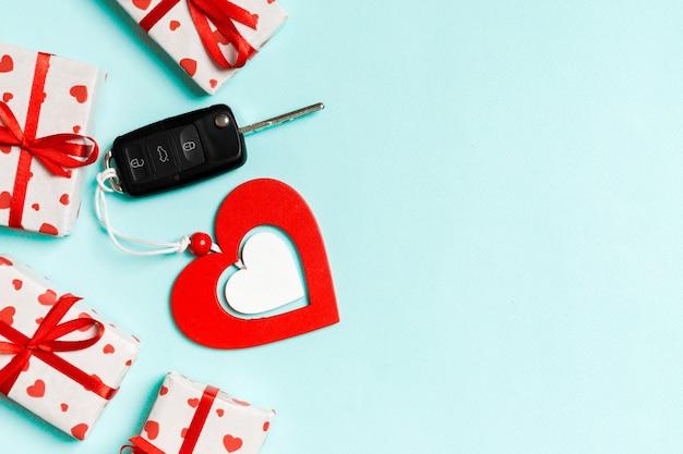 Vista dall'alto della chiave della macchina, scatole regalo e cuore in legno
