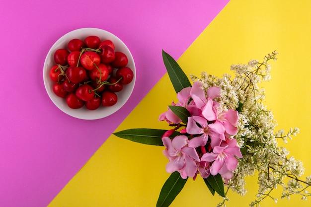Vista dall'alto della ciliegia in una ciotola con fiori su una superficie giallo-rosa