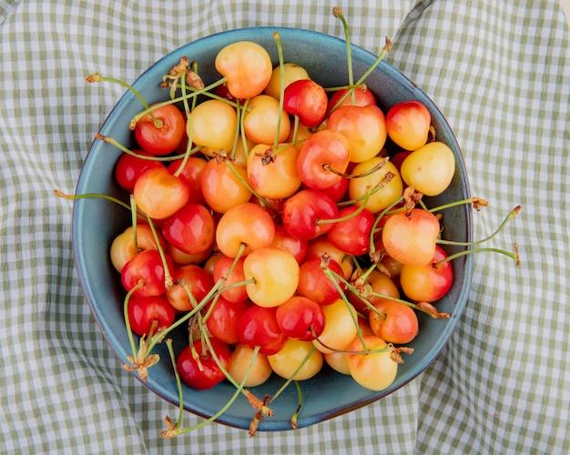 Vista dall'alto della ciotola con ciliegie sul panno plaid