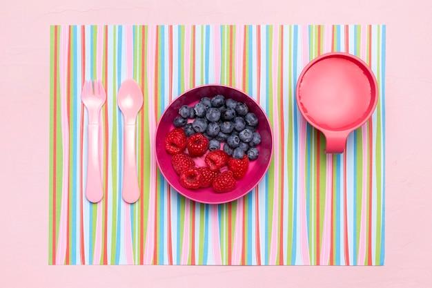 Vista dall'alto della ciotola con mirtilli e lamponi come alimenti per l'infanzia
