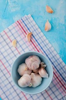 Vista dall'alto della ciotola piena di bulbi di aglio con spicchi d'aglio intorno sul panno su sfondo blu