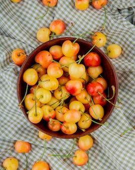 Vista dall'alto della ciotola piena di ciliegie gialle e rosse sul panno plaid