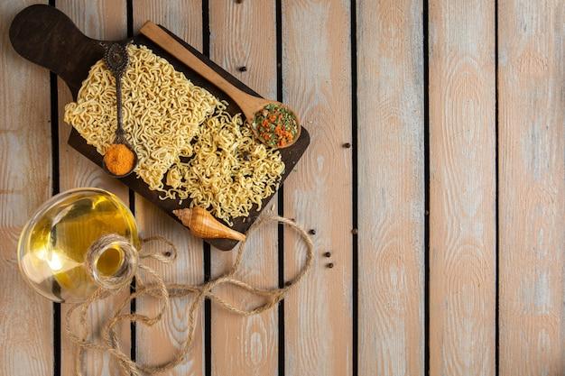 Vista dall'alto della composizione con pasta istantanea cruda con spezie guscio e una bottiglia di olio d'oliva