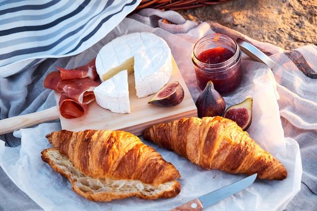 Vista dall'alto della composizione romantica bella picnic con croissant, pane, marmellata, formaggio, fichi e jamon.