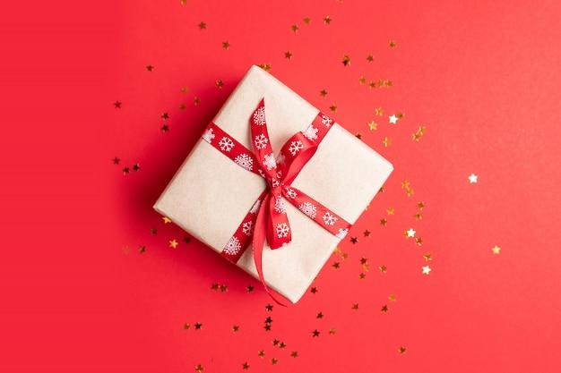Vista dall'alto della confezione regalo con decorazione di stelle d'oro su rosso. minimo per compleanno, festa della mamma o matrimonio.