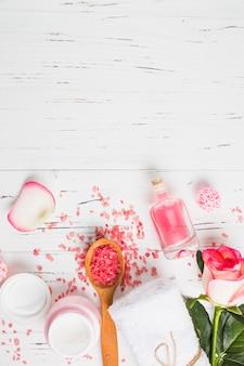 Vista dall'alto della crema idratante; bottiglia d'olio; fiore; sale e asciugamano su fondo in legno