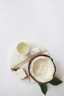 Vista dall'alto della crema idratante; noce di cocco e olio sul bordo di marmo bianco