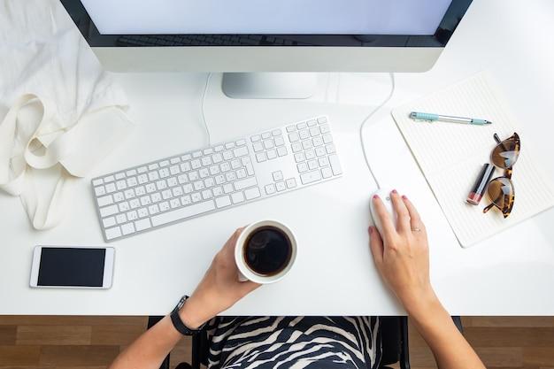 Vista dall'alto della donna d'affari in ufficio minimalista. concetto di lay flat di vita in ufficio: persona di sesso femminile con caffè davanti al computer desktop sul posto di lavoro