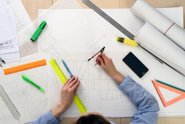 Vista dall'alto della donna dell'architetto al lavoro sul design dell'edificio, sul tavolo, righelli, matite, bussola, smartphone, disegno contorto.