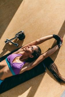 Vista dall'alto della donna sportiva che allunga le braccia mentre giaceva sul pavimento in una palestra. accanto al suo kettlebell e ai suoi manubri.