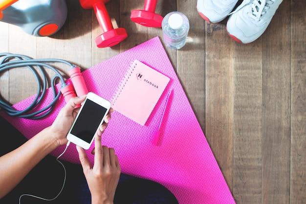 Vista dall'alto della donna utilizzando il telefono cellulare per allenamento fitness online con attrezzature per il fitness