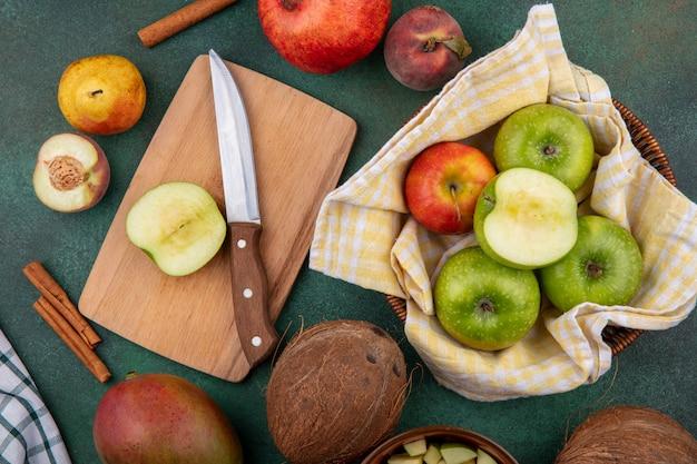 Vista dall'alto della fetta di mela sulla tavola di legno con coltello con diverse mele e frutti come la pera pesca melograno su gre