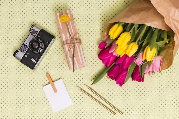 Vista dall'alto della fotocamera retrò; foglio bianco; matite; confezione regalo e bouquet di fiori di tulipano sopra sfondo giallo a pois