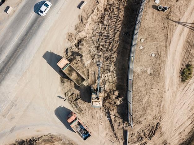 Vista dall'alto della macchina dell'escavatore scavare il terreno e metterlo in autocarro con cassone ribaltabile industriale