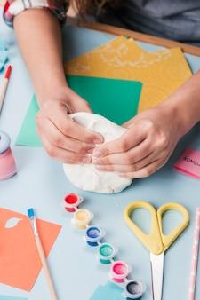 Vista dall'alto della mano che impastano argilla bianca per fare arte creativa