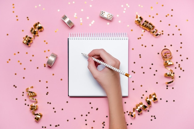 Vista dall'alto della mano che scrive una lista dei desideri del nuovo anno