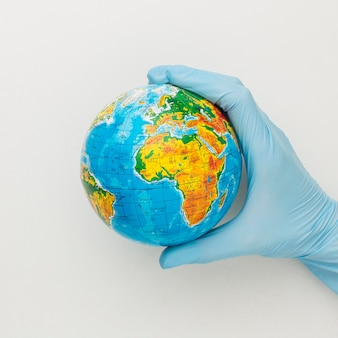 Vista dall'alto della mano con guanti che tengono il globo